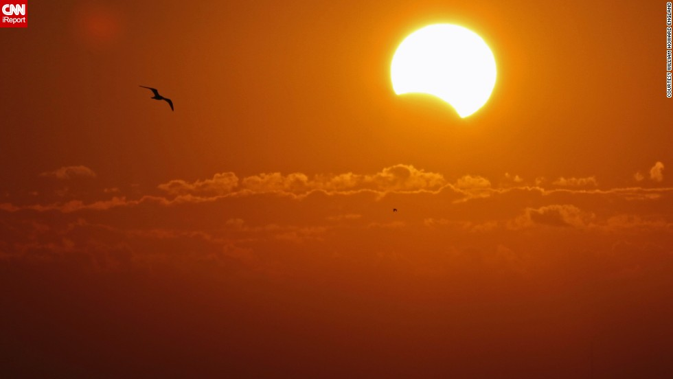 "<a href=""http://ireport.cnn.com/docs/DOC-1055901"">William England</a> could not see the eclipse with his naked eye while out in Titusville, Florida. But he took photos of the sunrise anyway. Only later did he realize he captured the solar event through his camera."