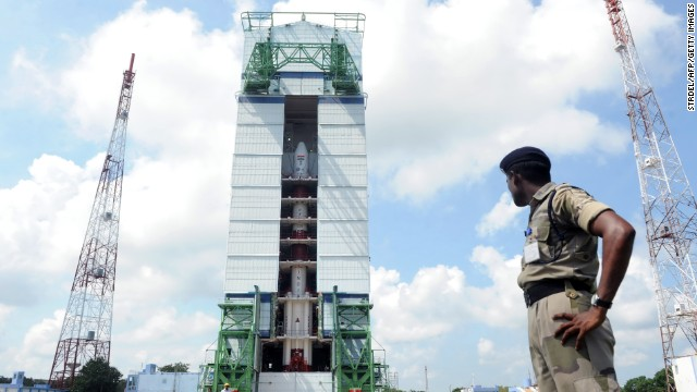 This photograph taken on October 30, 2013 shows an Indian security forces member keeping watch near the PSLV-C25 launch vehicle, carrying the Mars Orbiter probe as its payload, at the Indian Space Research Organisation facility in Sriharikota, ahead its planned launch on November 5. The unmanned probe, weighing 1.35 tonnes and about the size of a large refrigerator, will leave earth strapped to an Indian rocket which is set to blast off from the south-east coast on November 5 afternoon. AFP PHOTO/STR (Photo credit should read STRDEL/AFP/Getty Images)