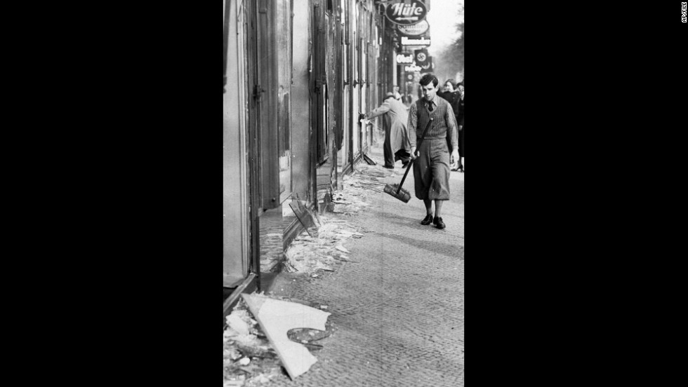 "A young man prepares to clean up broken window glass in Berlin. During ""Kristallnacht,"" about 30,000 Jewish men between the ages of 16 and 60 were arrested and taken to concentration camps."