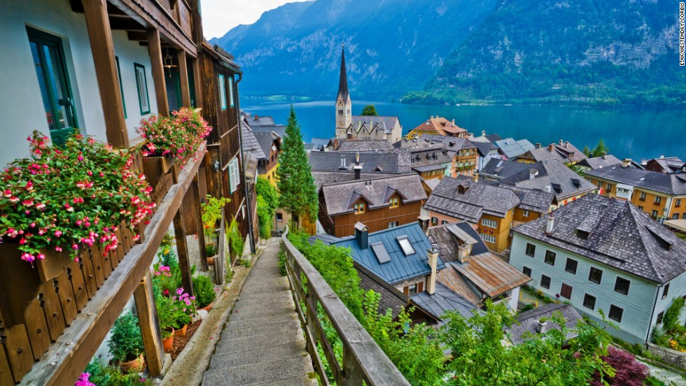 The idyllic town of Hallstatt is located between a pristine lake and a lush mountain rising from the water's edge.