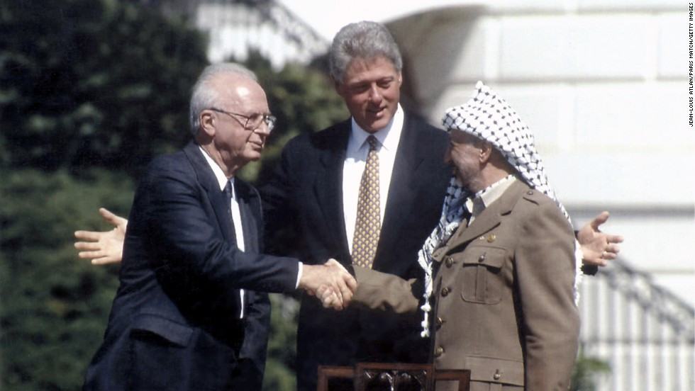 With U.S. President Bill Clinton watching, Arafat shakes hands with Israeli Prime Minister Yitzhak Rabin after the two signed the Oslo peace accord in Washington on September 13, 1993.