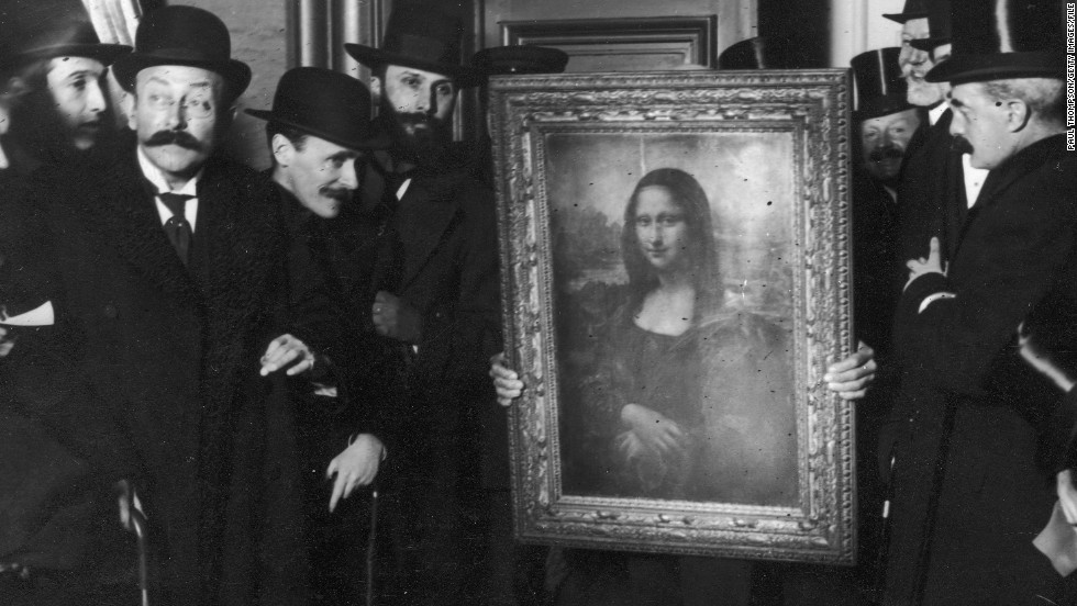 Officials crowd around the Mona Lisa upon her return to the Louvre in January 1914. Why such a fuss? She'd been missing for over two years.