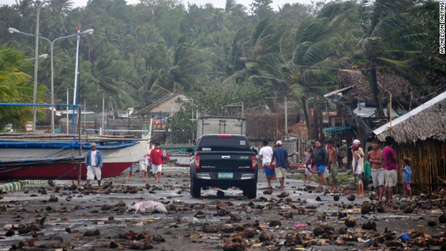 Debris litter the road by the coastal village in Legazpi city following a storm surge brought about by powerful Typhoon Haiyan in Albay province Friday, Nov. 8, 2013, about 520 kilometers ( 325 miles) south of Manila, Philippines. The strongest typhoon this year slammed into the central Philippines on Friday, setting off landslides and knocking out power and communication lines in several provinces. (AP Photo/Nelson Salting)