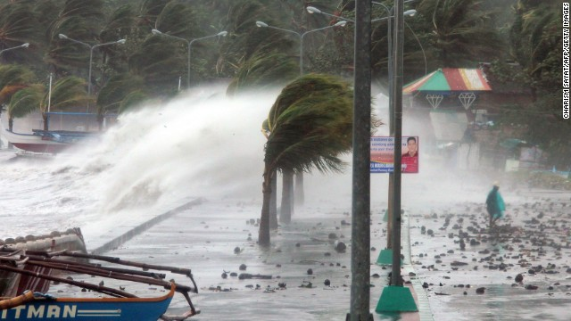 A resident (R) walks past high waves pounding the sea wall amidst strong winds as Typhoon Haiyan hit the city of Legaspi, Albay province, south of Manila on November 8, 2013. One of the most intense typhoons on record whipped the Philippines on November 8, killing three people and terrifying millions as monster winds tore roofs off buildings and giant waves washed away flimsy homes.AFP PHOTO/CHARISM SAYAT (Photo credit should read Charism SAYAT/AFP/Getty Images)