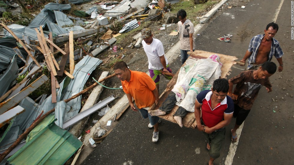 People in Tacloban carry a victim of the typhoon November 9.