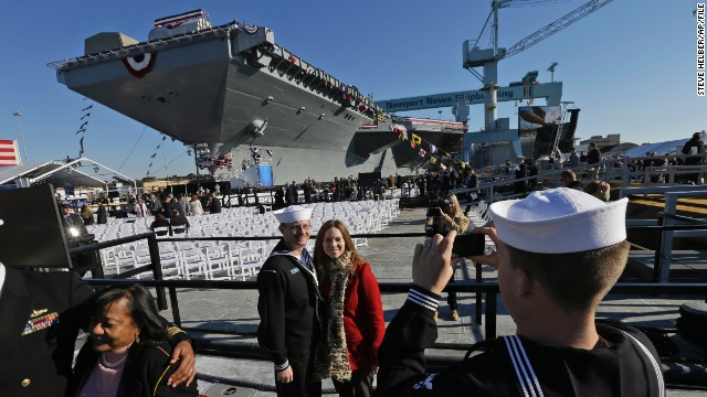 U.S. Navy Bosun's  mate, Ben Hansen and his wife Jessica, of Edmore Mich., are photographed in front of the Navy's newest nuclear powered aircraft carrier USS Gerald R. Ford for the christening of the ship at the Newport News Shipbuilding in Newport News, Va., Saturday, Nov. 9, 2013. Former President Ford's daughter Susan Ford Bales will christen the ship.