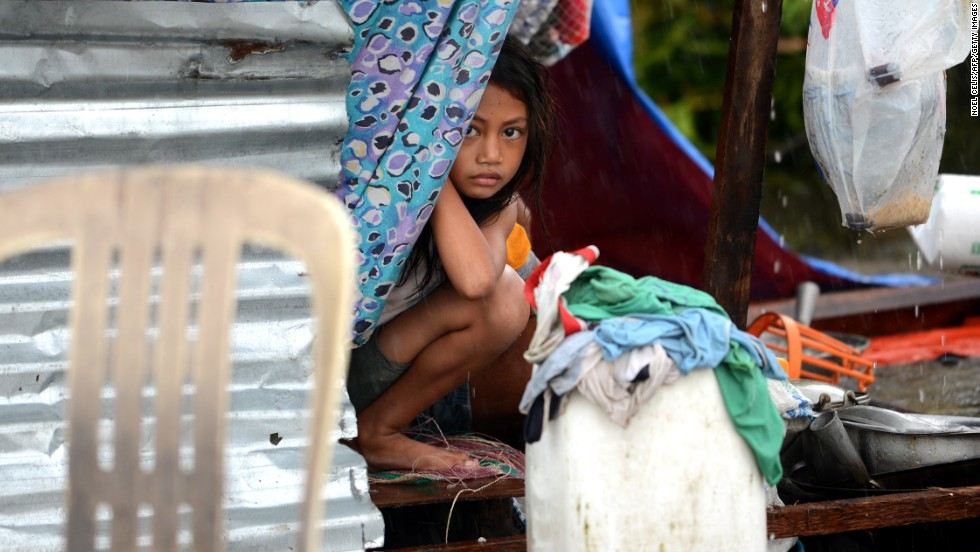 A girl peeks out from a makeshift shelter in Tacloban.