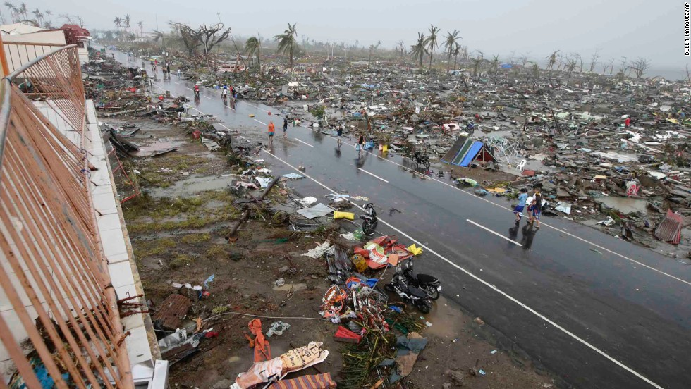 People walk past the Tacloban devastation on November 10.