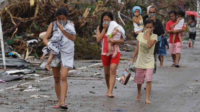 People cover their noses from the smell of dead bodies in Tacloban.