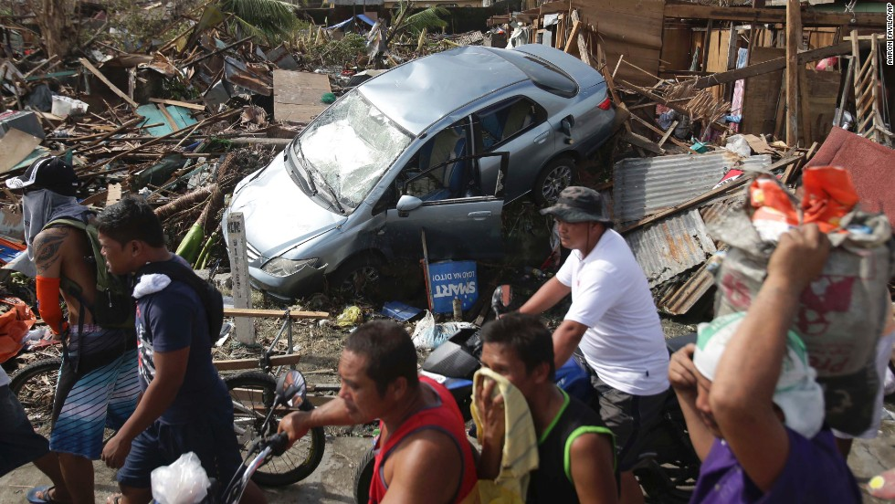 People in Tacloban pass debris on November 11.
