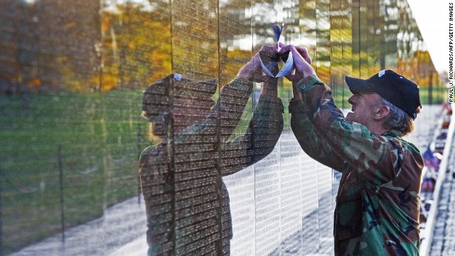 A man traces the name of a fallen soldier off the wall of Vietnam War Memorial.