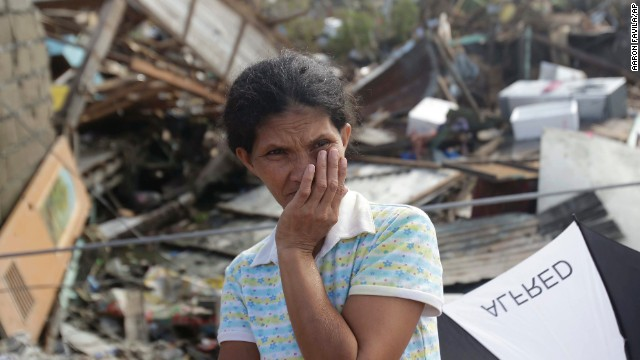 A survivor stands outside her damaged house at typhoon ravaged Tacloban city, Leyte province, central Philippines on Monday, Nov. 11, 2013. Authorities said at least 2 million people in 41 provinces had been affected by Friday's disaster and at least 23,000 houses had been damaged or destroyed.  (AP Photo/Aaron Favila)