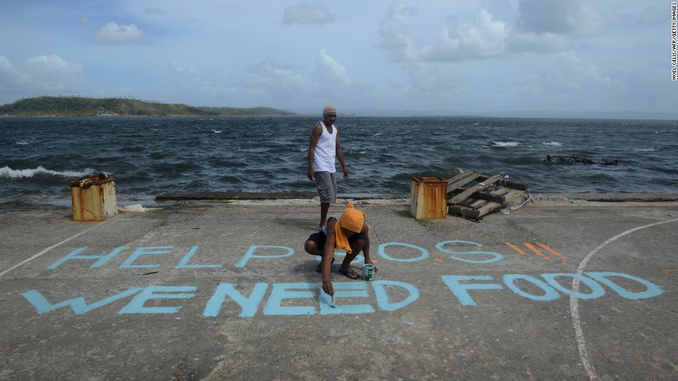 A man seeking aid paints a message on a basketball court November 11 in Anibong, Philippines.
