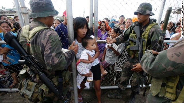 A woman carries her child through a fence to get food from relief workers on November 11 outside the Tacloban airport.