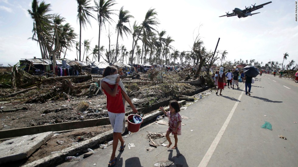 Survivors walk through the streets of Tacloban as a military plane flies overhead on November 11.