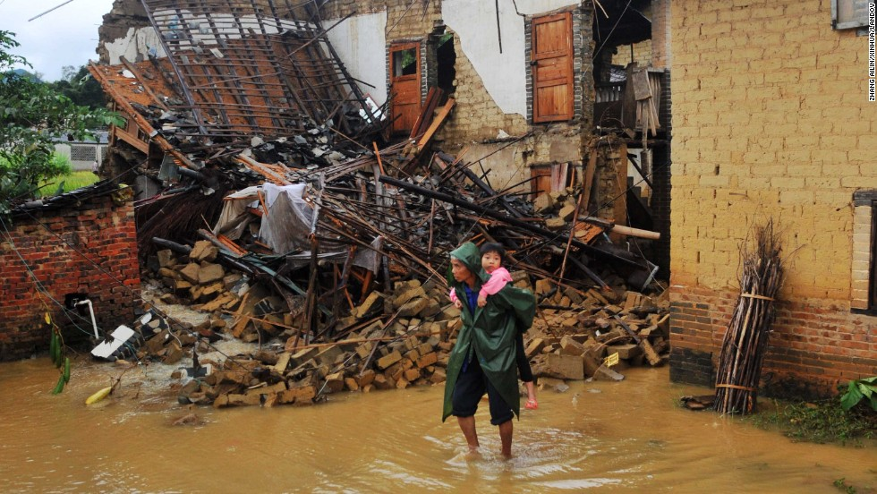 A woman carries a child through a flooded street in Yong'an, China, on November 11. China and Vietnam were also hit hard by the storm.