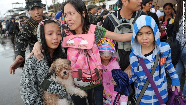 A mother (C) cries after her family failed to take a flight on a C-130 military plane out of Tacloban, Leyte province, central Philippines on November 12, 2013