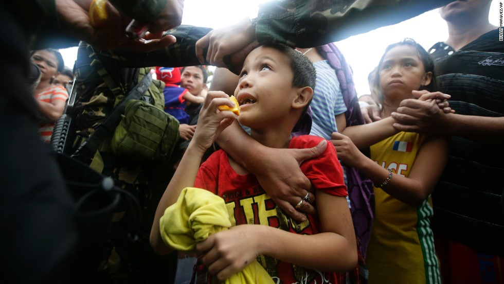 A Philippine air force officer hands out orange slices to typhoon survivors as they line up to board a military transport plane November 12 in Tacloban.