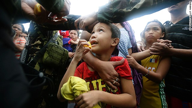 A Philippine air force officer hands out orange slices to typhoon survivors as they line up to board a C-130 military transport plane , Tuesday Nov. 12, 2013, in Tacloban city, central Philippines.