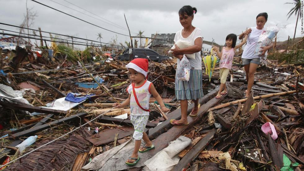 People walk through damage in Tacloban on November 12.