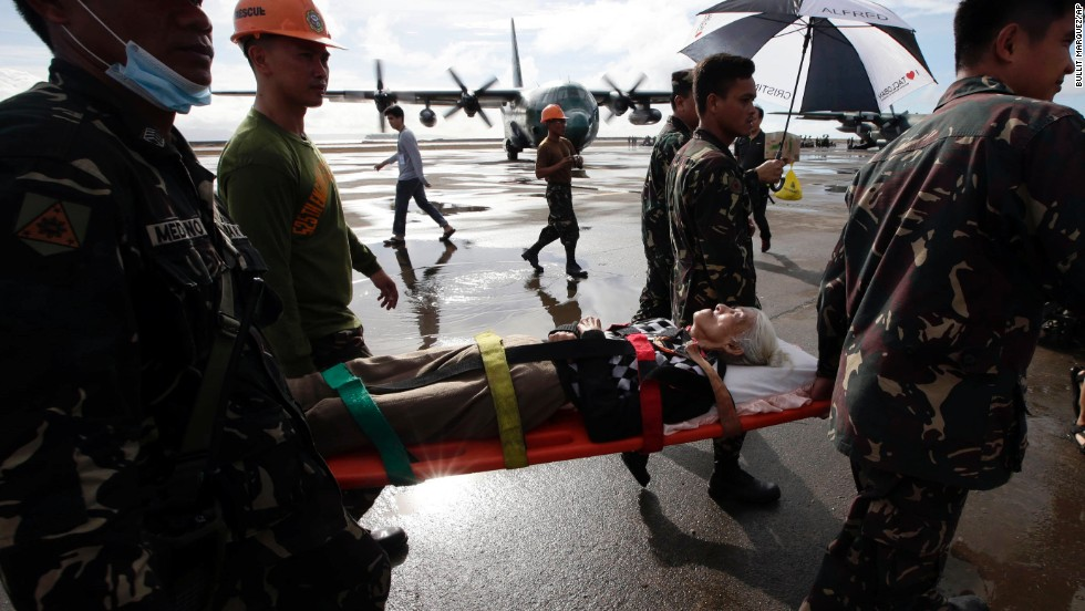 An injured survivor gets carried on a stretcher before being airlifted from Tacloban's airport November 13.