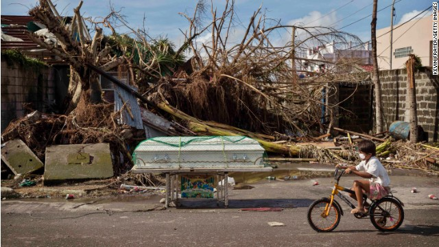 A boy cycles past a coffin left on a streen in Tacloban, Philippines on November 13.