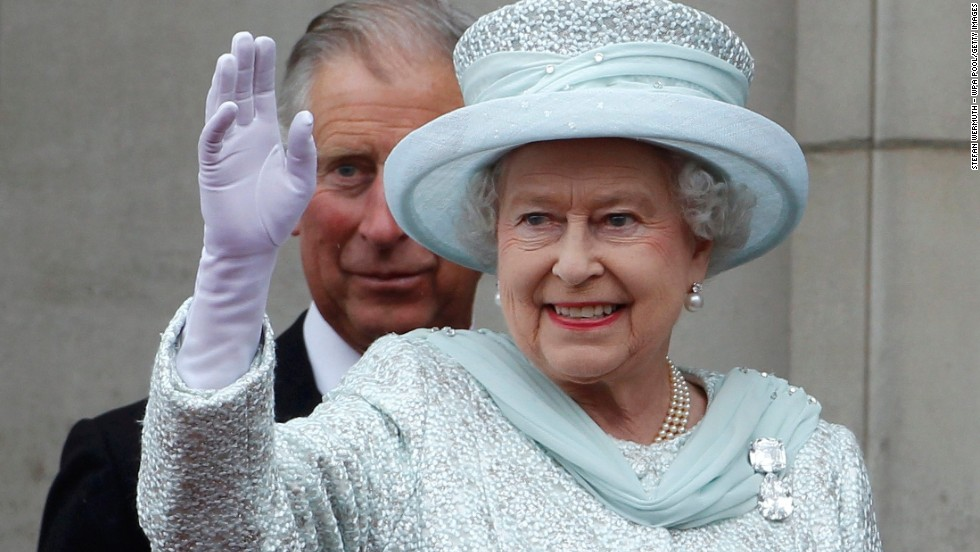 The Queen waves from the balcony of Buckingham Palace as Charles, stands behind her, during the finale of the Queen's Diamond Jubilee celebrations on June 5, 2012, in London.