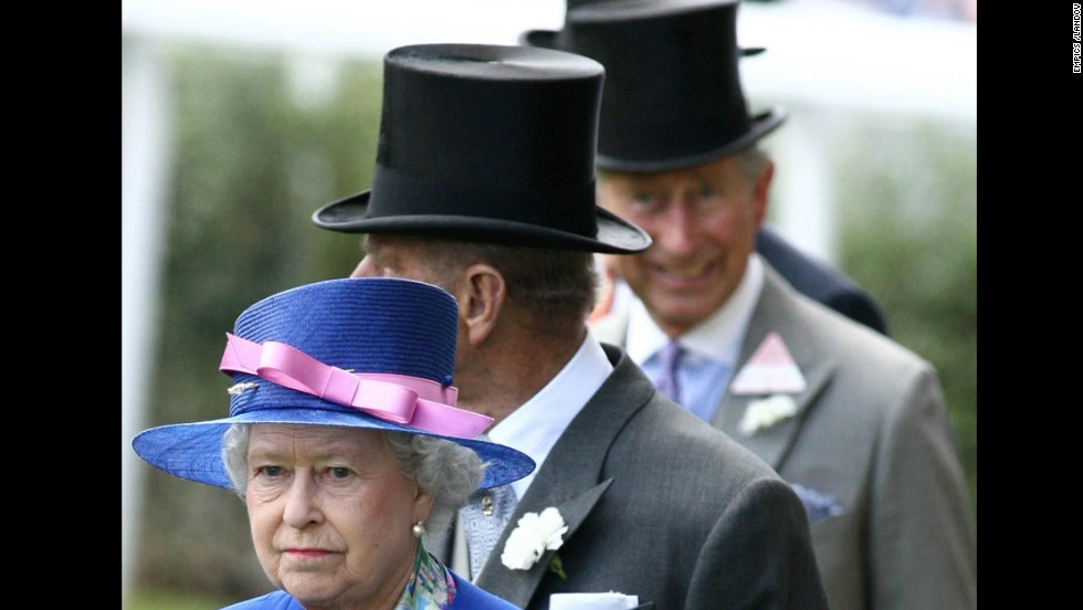 Charles, out of focus, smiles at the camera while following his mother and his father, Prince Phillip, Duke of Edinburgh. for the first day of the royal meeting at the new state-of-the-art course at Ascot in Berkshire in June 2006.