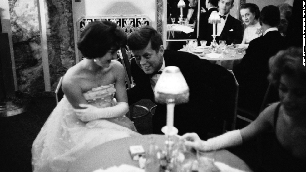 Kennedy lends an ear to his wife as they sit together at a table during cocktail hour before dining at a society gala at the Walford Astoria Hotel in 1960.