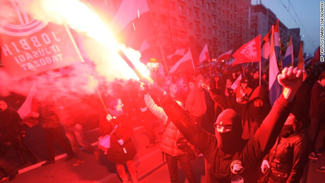 People hold burning flares as they march through the the centre of Warsaw, Poland on Monday,  November 11.