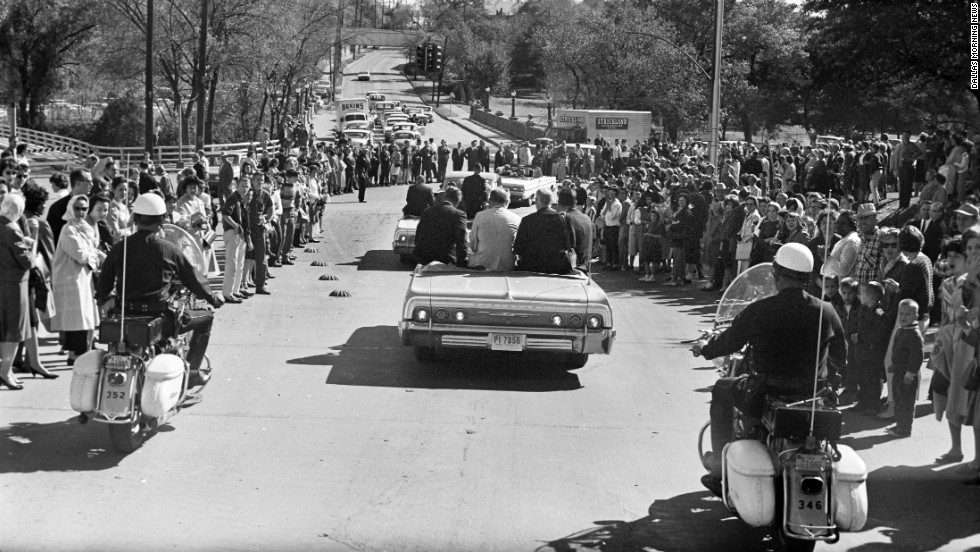 Crowds line the street as Kennedy's motorcade heads toward downtown Dallas. A group of White House staffers follows the motorcade in a bus several vehicles behind the presidential limousine.