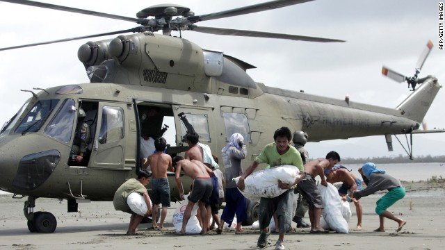 Survivors of Super Typhoon Haiyan at the coastal village of Capiz in the central Philippines carry sacks containing relief goods delivered via helicopter by the Armed Forces of the Philippines (AFP) on November 11, 2013.