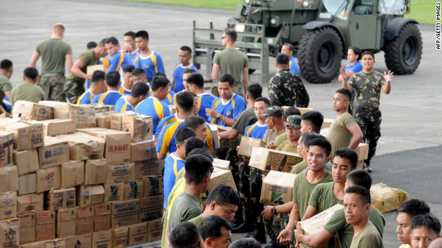 US and Philippine military personnel prepare relief goods for transporting at the military base in Manila on November 12, 2013, before sending the packages to the central coastal city of Tacloban which bore the brunt of Super Typhoon Haiyan when it swept through the central Philippines this weekend.