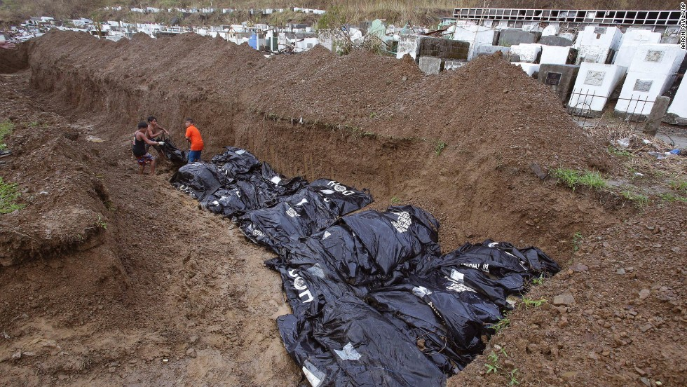 Workers arrange bodies at a mass burial site at a Tacloban cemetery November 14.