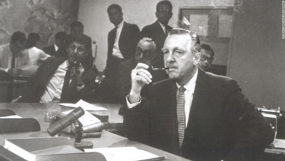 "Walter Cronkite sits behind the news desk on the set of the ""CBS Evening News with Walter Cronkite,"" New York in August 1963.  Cronkite became the anchor of American network television's first nightly half-hour news program on September 2, 1963."