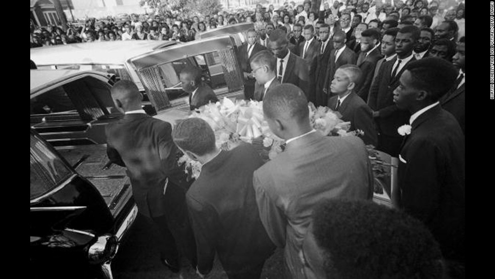 "A coffin is loaded into a hearse at a funeral for victims of the 16th Street Baptist Church bombing. The Birmingham Church Bombing, also known as ""Bloody Sunday,"" took place on September 15, 1963."