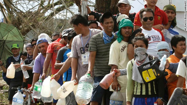Typhoon survivors line up to get fuel from an abandoned filling station Thursday, Nov. 14, 2013, in Tacloban city, Leyte province in central Philippines. Aid has been slow to reach the half-million people displaced by the storm that tore across several islands in eastern Philippines last Friday. (AP Photo/Bullit Marquez)