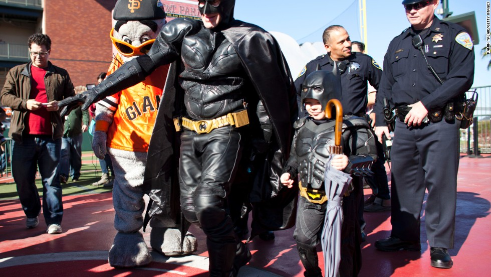 Miles, as Batkid, walks with Batman after releasing San Francisco Giants mascot Lou Seal from the Penguin as part of a Make-A-Wish foundation fulfillment at AT&T Park in November 2013.