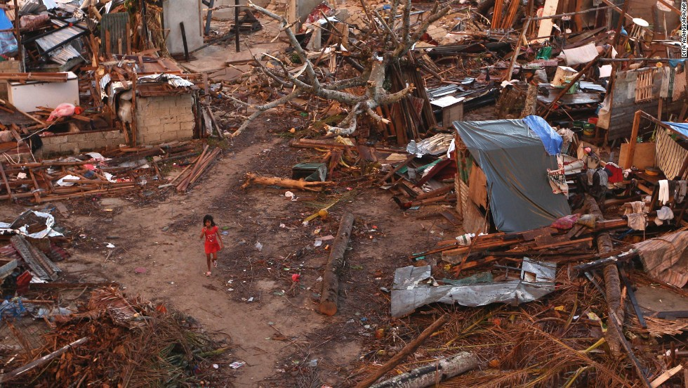 A young girl walks amid ruins of houses in a neighborhood badly affected by the typhoon in Guiuan, Philippines, on Friday, November 15.