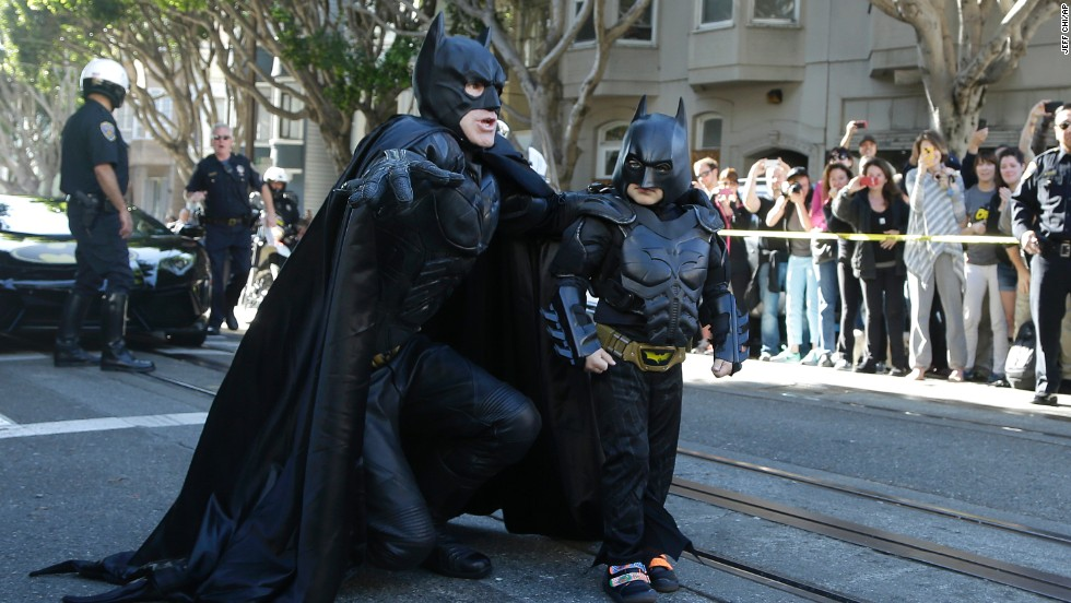 "Miles Scott, dressed as ""Batkid,"" right, walks with Batman before saving a damsel in distress in San Francisco, in November 2013. The City by the Bay turned into Gotham City on Friday, as city officials helped fulfill Scott's wish to be Batkid. Scott, a leukemia patient from Tulelake, California, was called into service by San Francisco Police Chief Greg Suhr to help fight crime. The event was part of The Greater Bay Area Make-A-Wish Foundation."