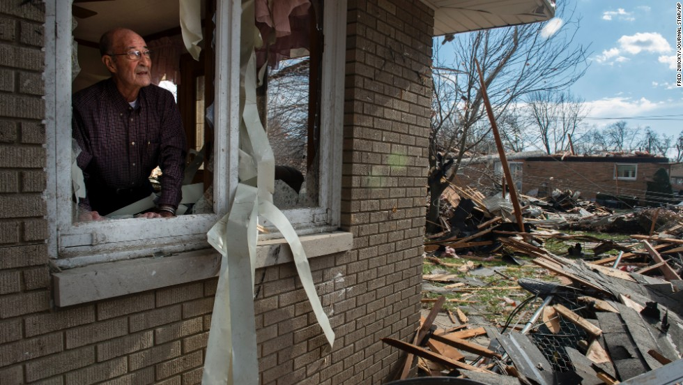 Chuck Phillips looks out at the destruction that tore off part of his roof and destroyed homes in his neighborhood on November 17 in Pekin.