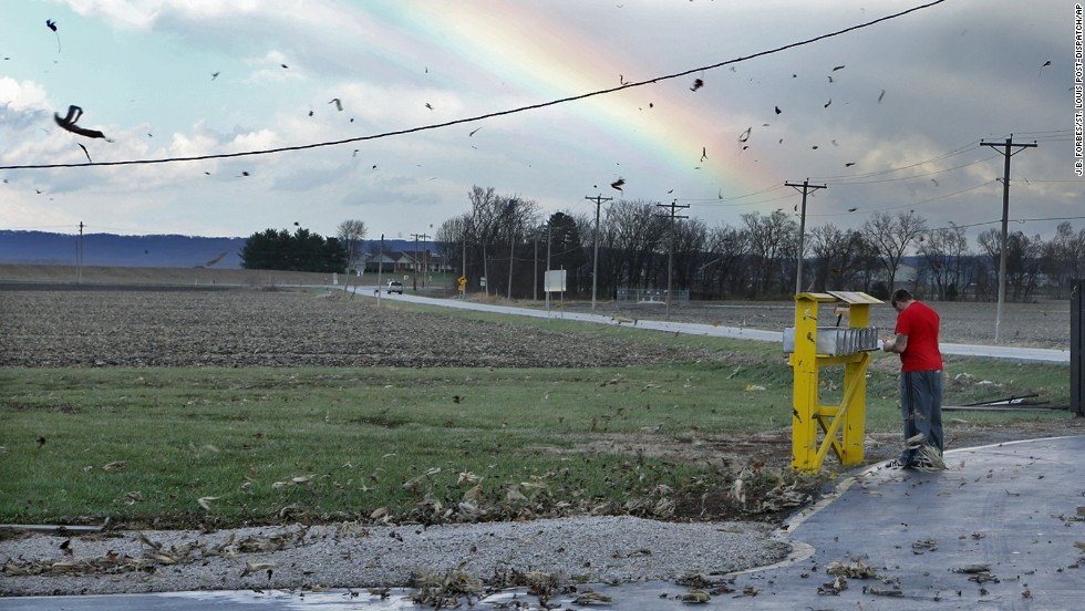 Corn husks fly through the air as Eric Crawford checks his mail after the storm passed in rural Orchard Farm, Missouri, on November 17.