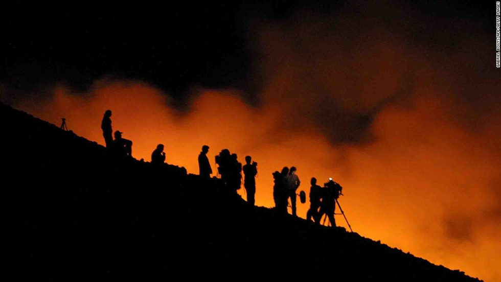 Reporters watch lava flow down Etna in 2001.