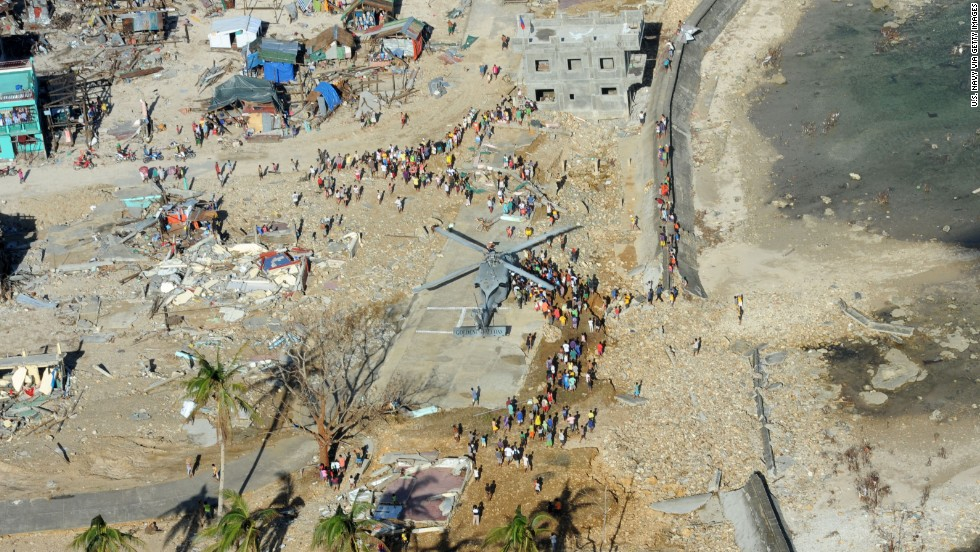 People gather around a helicopter as it delivers relief supplies November 17 in Guiuan, Philippines.