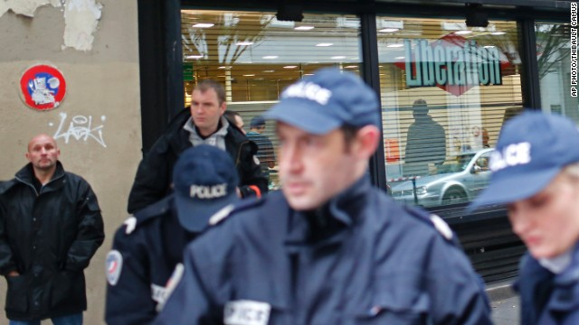 Police officers stand outside Liberation newspaper office in Paris, Monday, Nov. 18, 2013, after a gunman opened fire in the lobby, wounding a photographer's assistant before fleeing. Fabrice Rousselot, editor of the daily newspaper Liberation said the 27-year-old victim was in serious condition. (AP Photo/Thibault Camus)