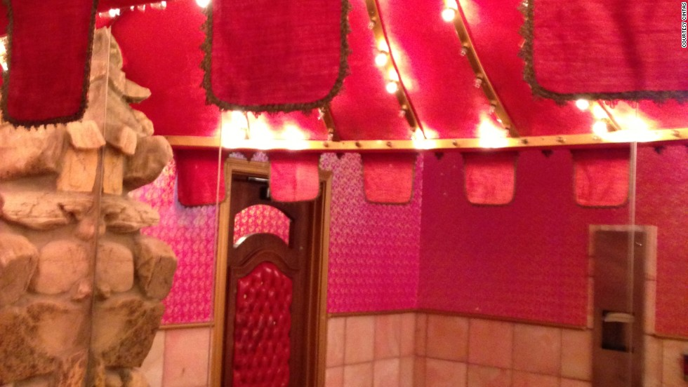 The ladies' room at the Alex Madonna Gold Rush Steak House has native stone walls, marble countertops, carved wood stall doors with pink leather and a ceiling chandelier.