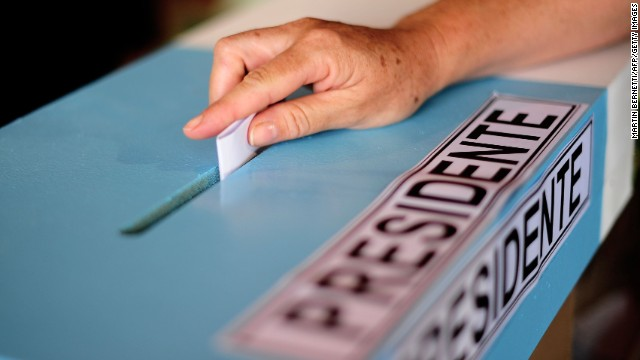 A woman casts her vote at a polling station during the general election in Santiago on November 17, 2013. Polls opened at 10h00 GMT, with some 9 million Chileans registered to vote.