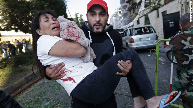 An injured woman is carried away from the scene in Beirut.