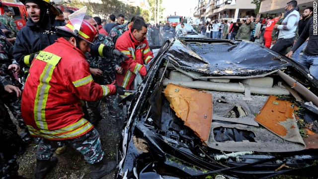 Lebanese Red Cross workers pull a body from a car.