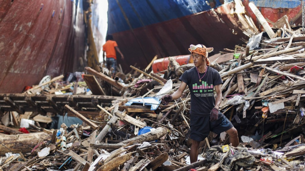 Survivors salvage wood next to stranded ships in Tacloban on November 19.
